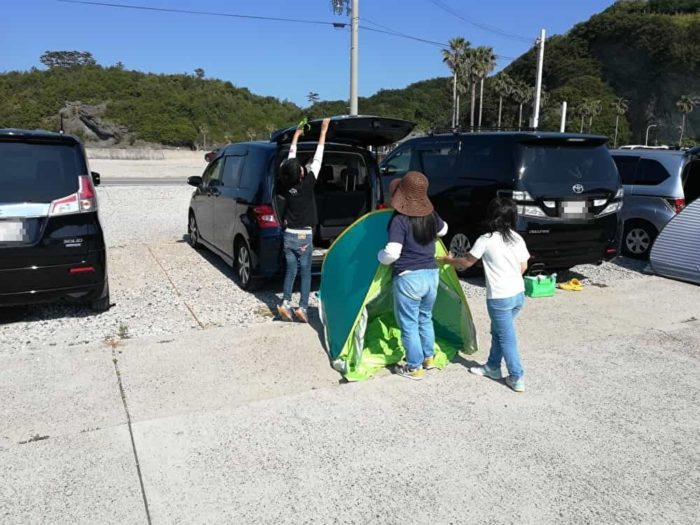 暑さ対策でテントを張る家族